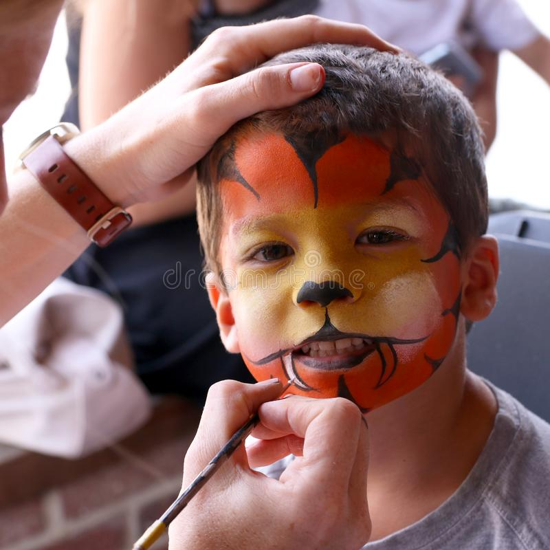 Little boy having his face painted stock image