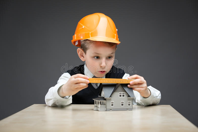 Little boy in headpiece with home model and ruler. Portrait of little boy in headpiece with home model and ruler on grey background. Concept of real estate and royalty free stock photo