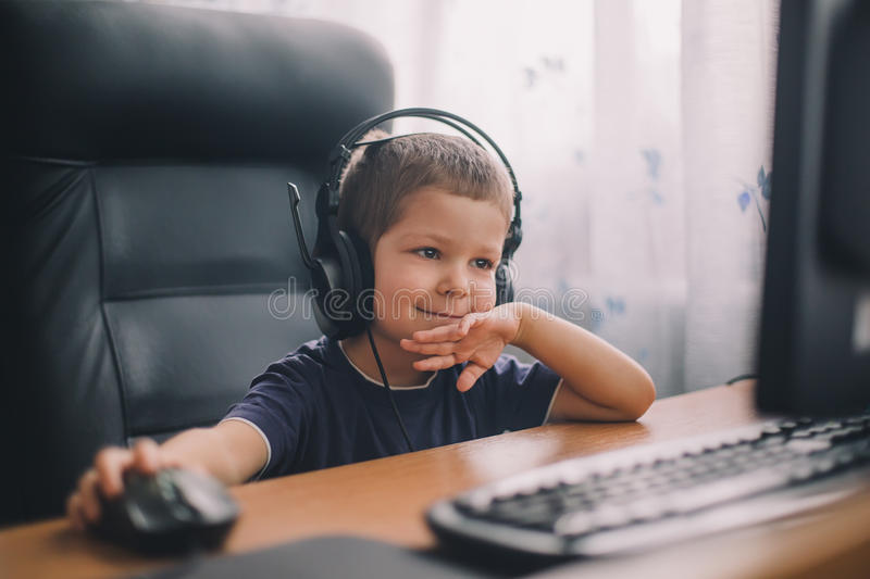 Little boy with headset using computer royalty free stock photography