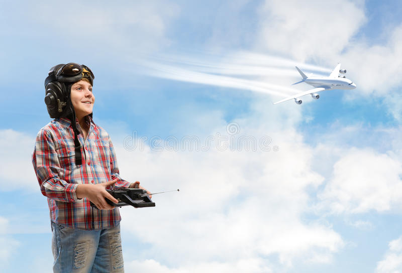 Boy dreams of becoming a pilot. Little boy in a helmet pilot keeps remote control, in the background plane and sky royalty free stock image