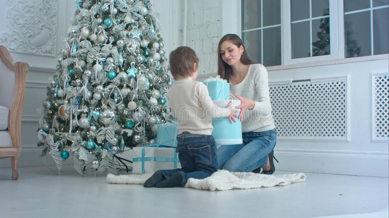 Little boy helping his mother to put gift boxes under Christmas tree royalty free stock images
