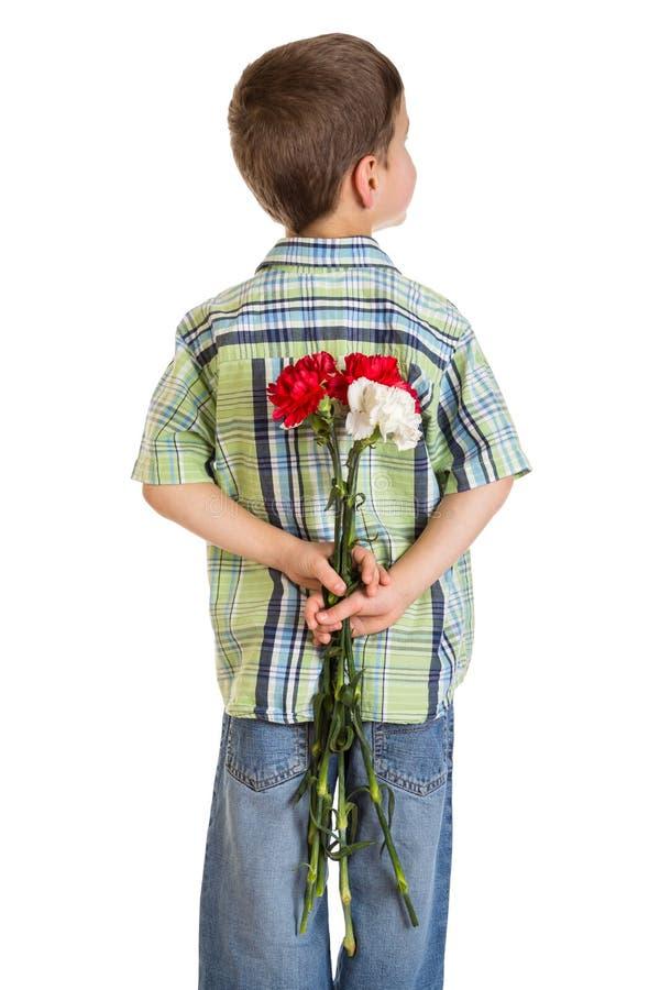 Little boy hiding carnations behind itself