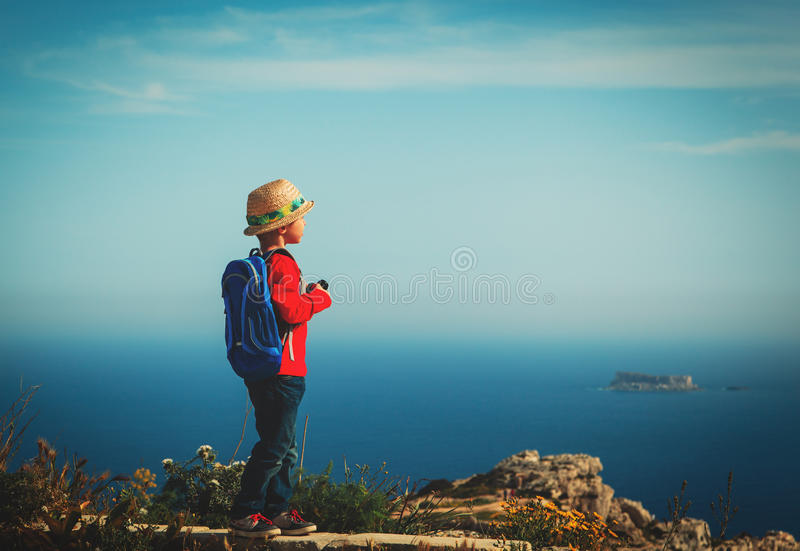 Little boy hiking in mountains, kids travel stock photo
