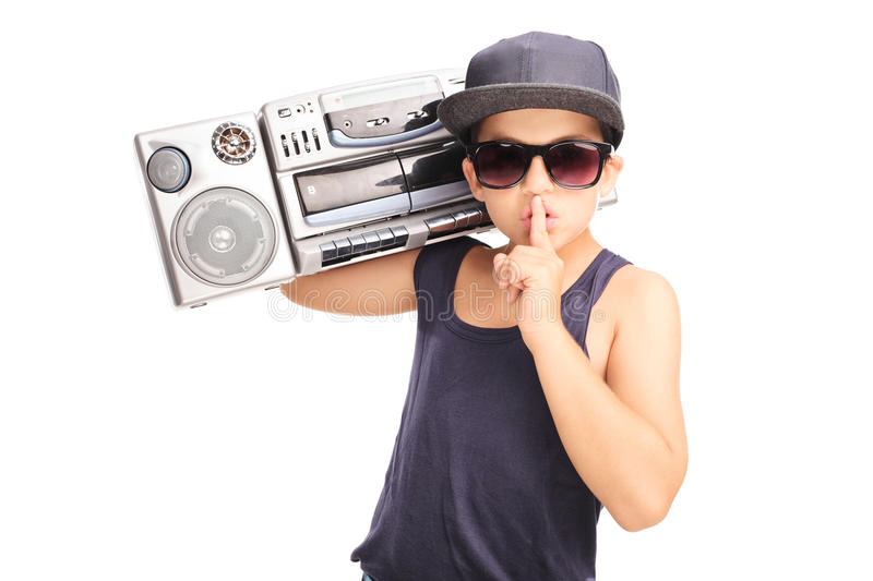 Little boy in hip-hop outfit carrying a ghetto blaster. And holding finger on his lips isolated on white background stock images