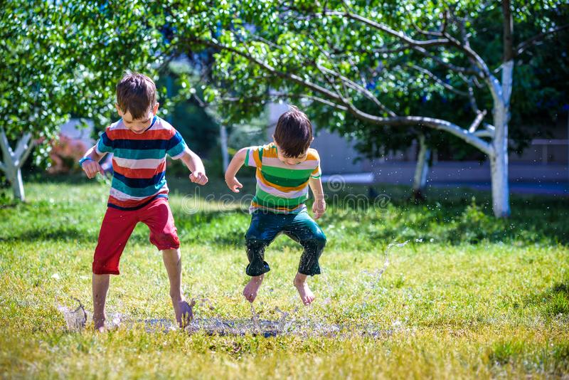 Little boy and his brother play in summer park. Children with colorful clothes jump in puddle and mud in the garden. stock photos