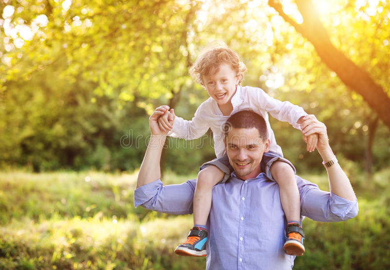 Little boy with his dad. Little boy and his dad enjoying their time together outside in nature royalty free stock images