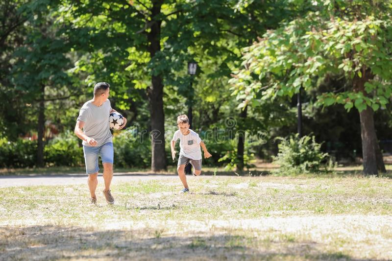 Little boy with his dad playing football outdoors royalty free stock images