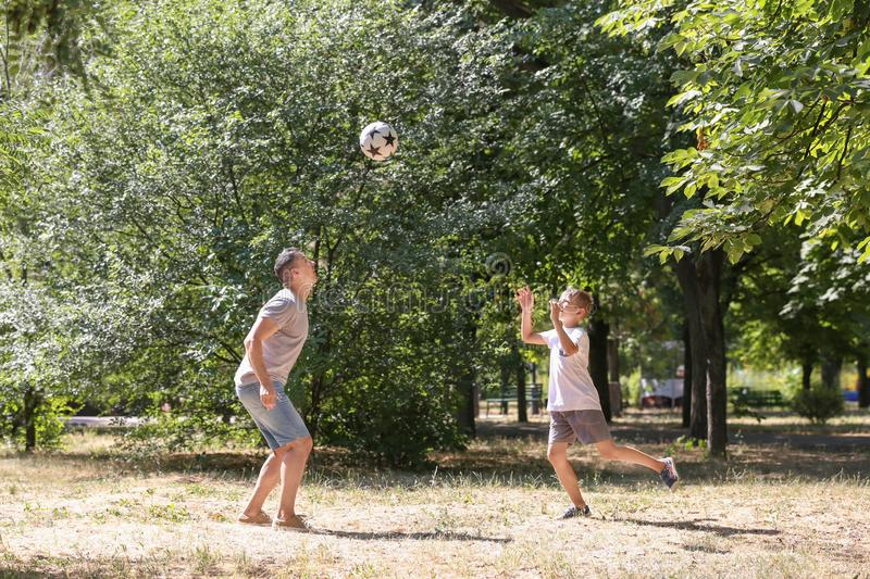 Little boy with his dad playing football outdoors stock photos