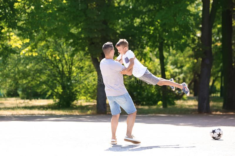 Little boy and his dad playing outdoors royalty free stock photo