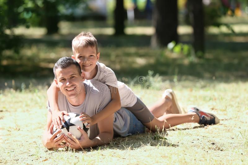 Little boy and his dad with soccer ball lying on grass outdoors stock photography