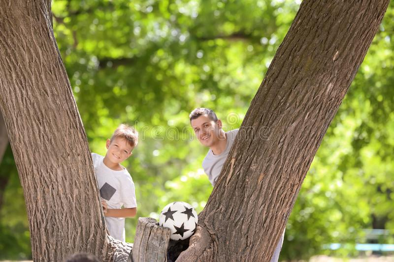 Little boy and his dad with soccer ball near tree outdoors royalty free stock photo