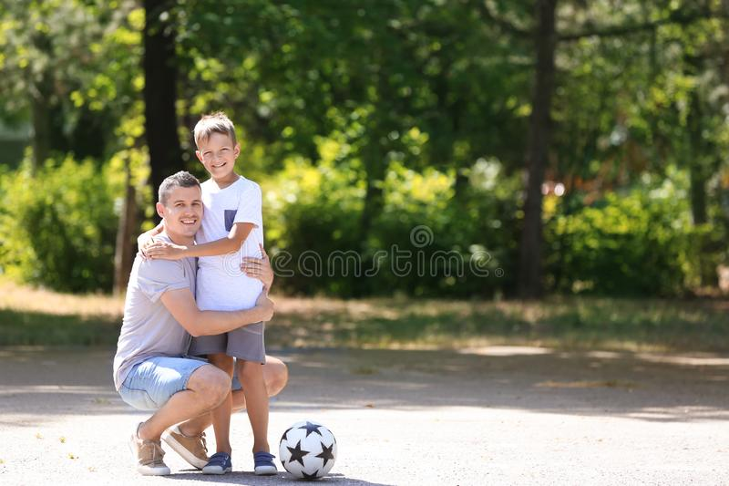 Little boy and his dad with soccer ball outdoors stock images