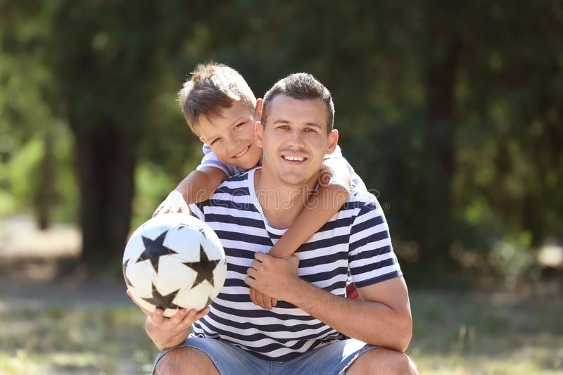 Little boy and his dad with soccer ball outdoors stock photos
