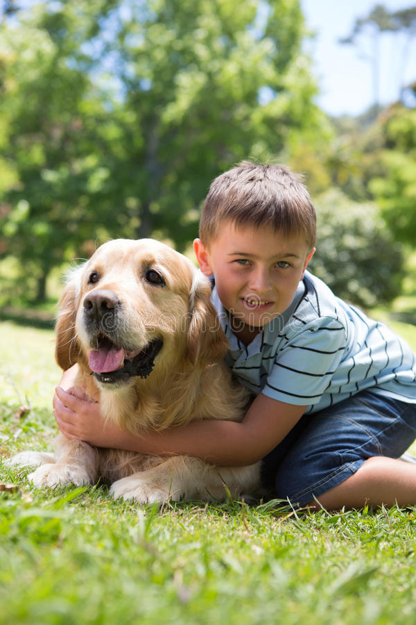 Little boy with his dog in the park. On a sunny day royalty free stock image