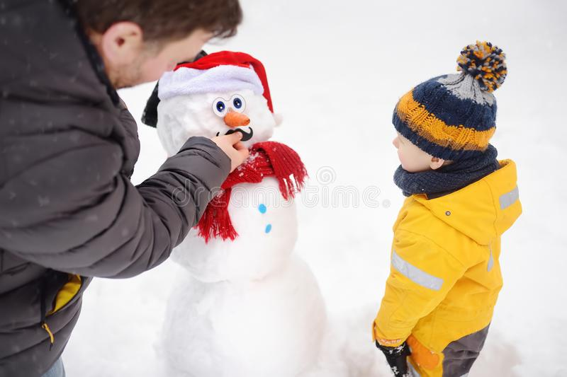 Little boy with his father building snowman in snowy park. Active outdoors leisure with children in winter stock image