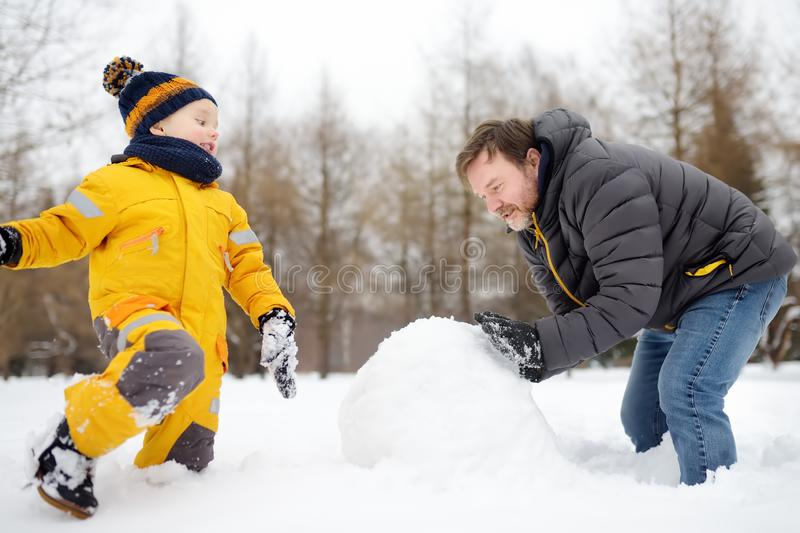 Little boy with his father building snowman in snowy park. Active outdoors leisure with children in winter stock images