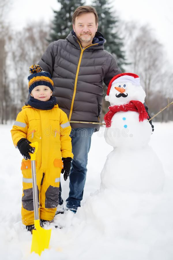 Little boy with his father building snowman in snowy park. Active outdoors leisure with children in winter royalty free stock images