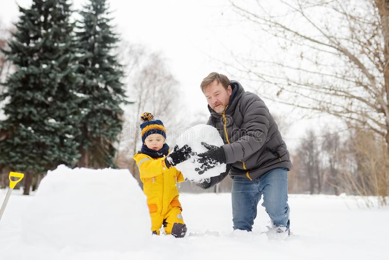Little boy with his father building snowman in snowy park. Active outdoors leisure with children in winter royalty free stock photo