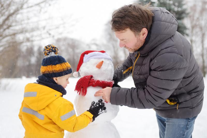 Little boy with his father building snowman in snowy park. Active outdoors leisure with children in winter royalty free stock image
