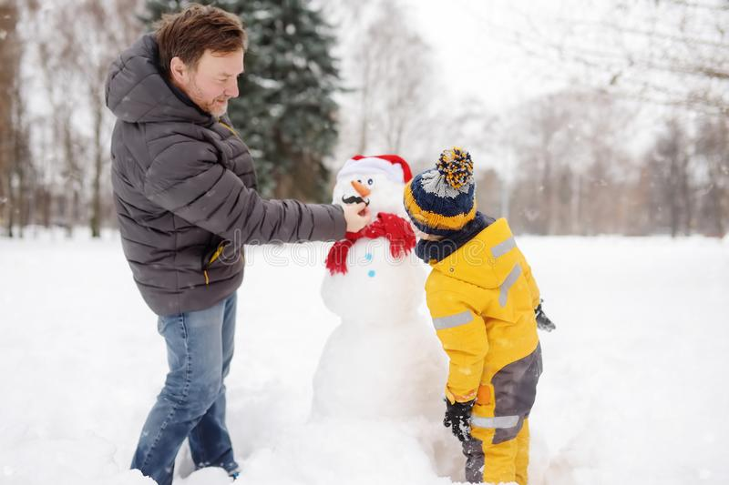 Little boy with his father building snowman in snowy park. Active outdoors leisure with children in winter royalty free stock photography