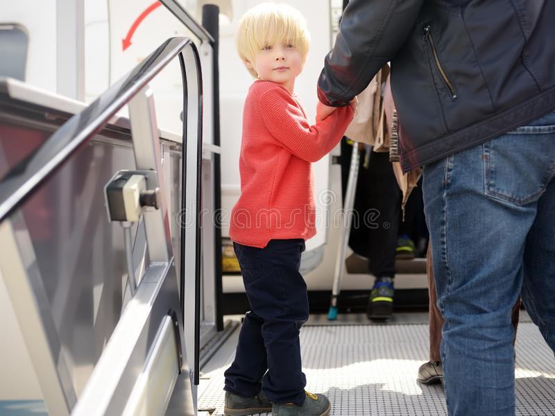 Little boy and his father climb the gangway into the plane against the background of people passenger. Back view royalty free stock photos