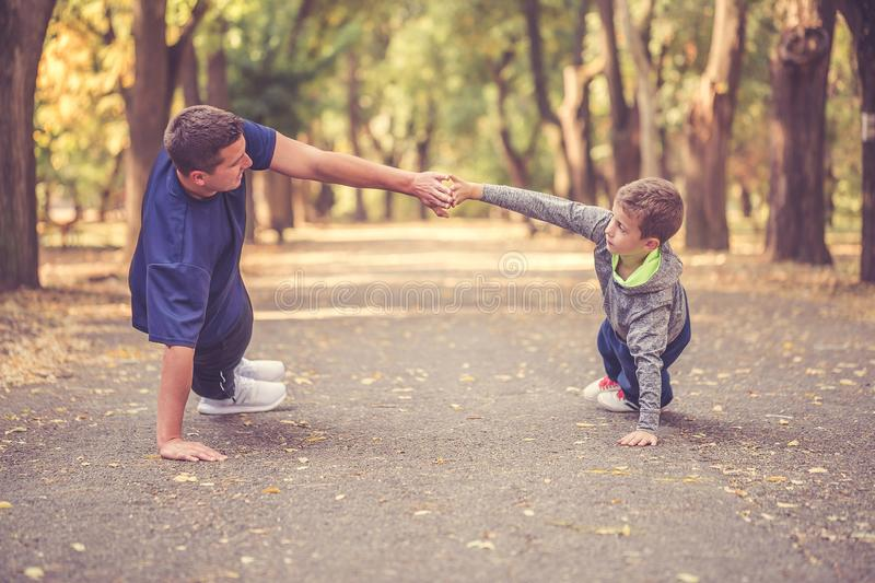 Little boy and his father exercising together outdoors royalty free stock images