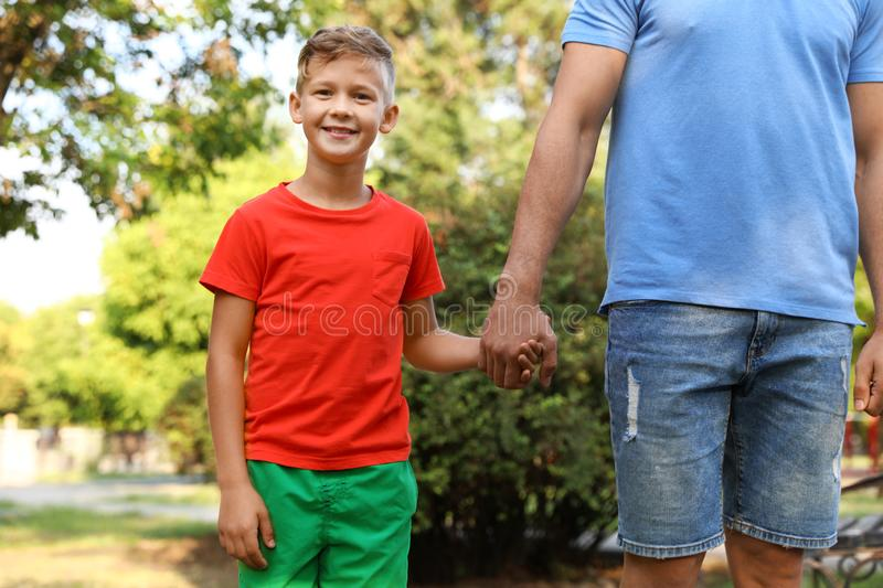 Little boy and his father holding hands. Family weekend stock image