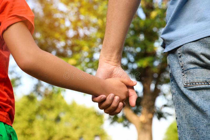 Little boy and his father holding hands outdoors. Family weekend stock image