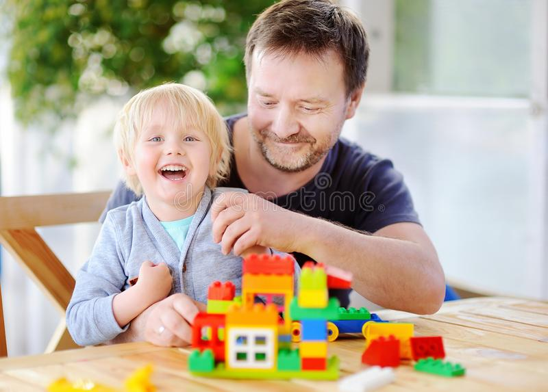 Little boy with his father playing with colorful plastic blocks at home stock photography