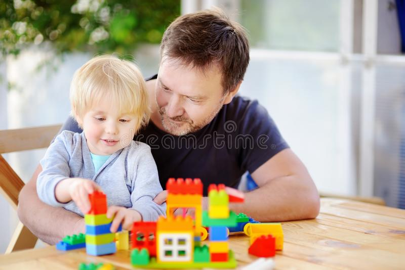 Little boy with his father playing with colorful plastic blocks at home royalty free stock image