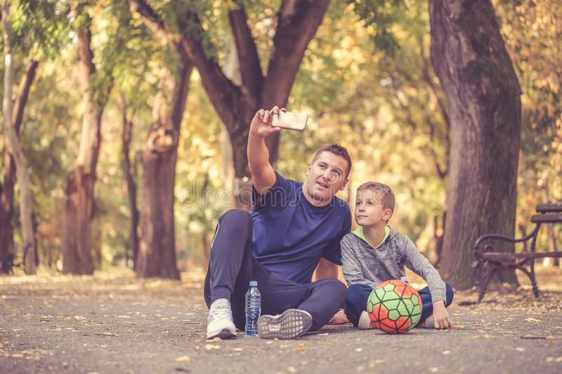 Little boy and his father taking a break and making selfie royalty free stock photos