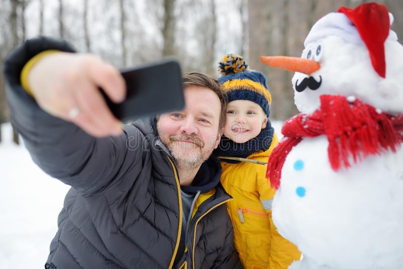 Little boy and his father taking selfie on background of snowman in snowy park. Active outdoors leisure with children in winter royalty free stock photography
