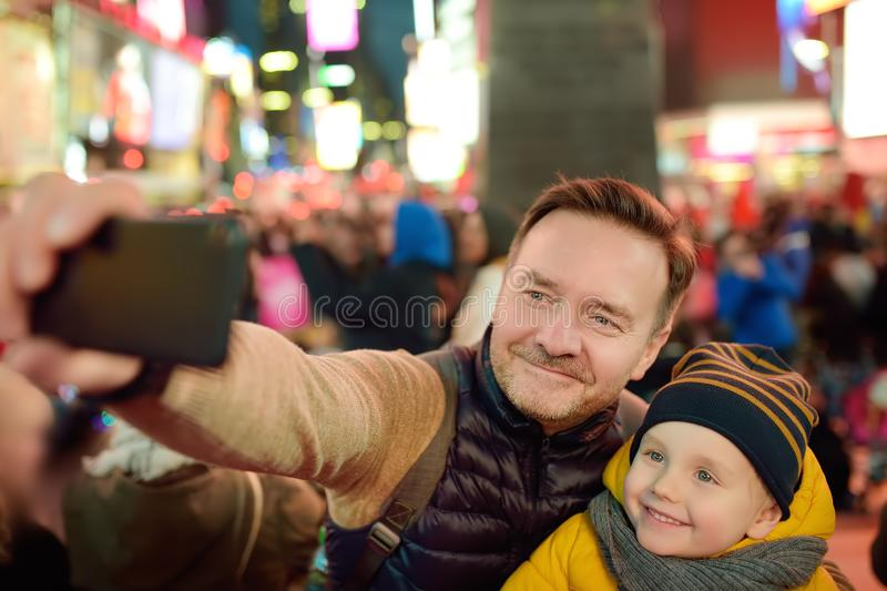 Little boy and his father taking selfie on Times Square in evening, downtown Manhattan royalty free stock image