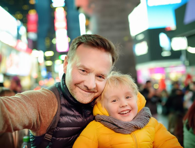 Little boy and his father taking selfie on Times Square in evening, downtown Manhattan royalty free stock photography