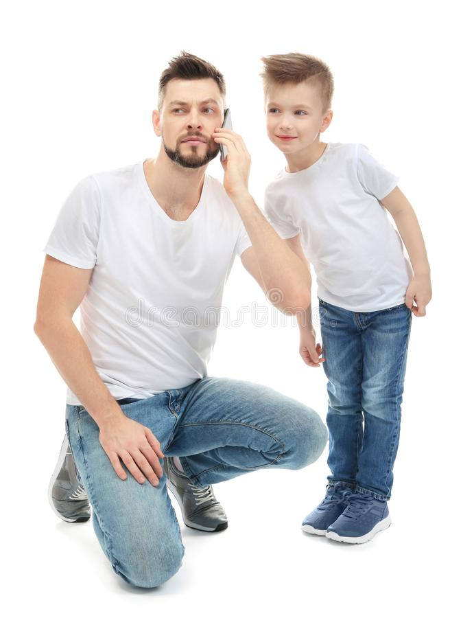 Little boy and his father talking by mobile phone stock image