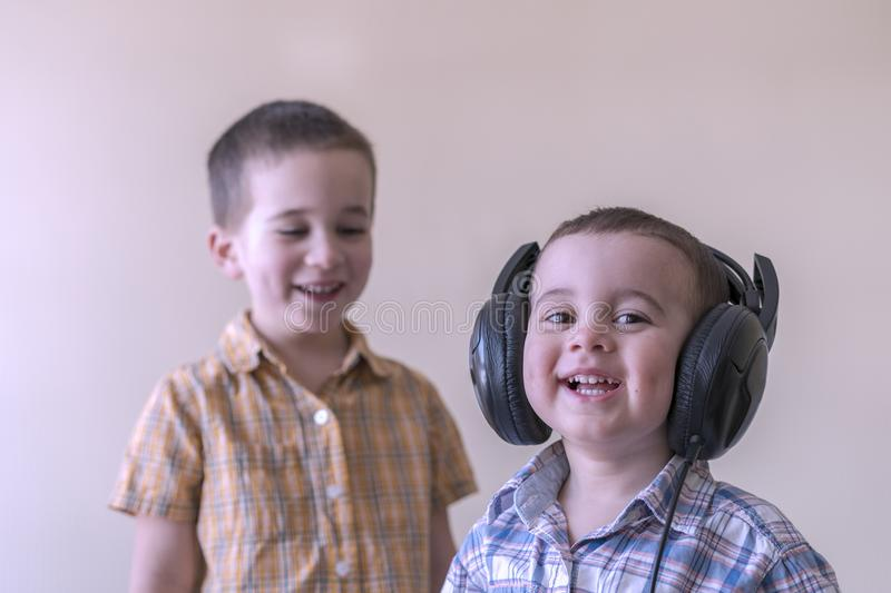 A little boy with his headphones dances with his brother. Two little brothers in shirts amuse themselves and dance. toned stock photos