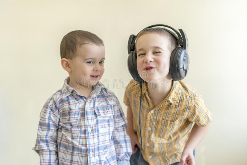 A little boy with his headphones dances with his brother. Two little brothers in shirts amuse themselves and dance. royalty free stock images