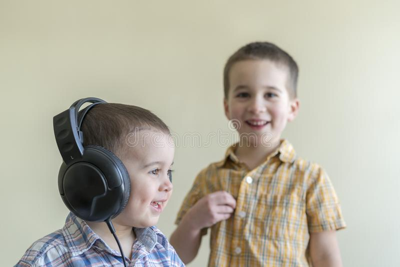 A little boy with his headphones dances with his brother. Two little brothers in shirts amuse themselves and dance. royalty free stock photo