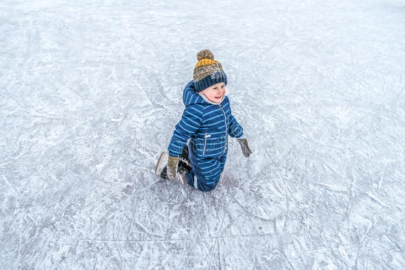 A little boy is on his knees, in winter, on a skating rink in winter overalls and a hat, he is smiling happily, first. A little boy is on his knees, in winter stock images