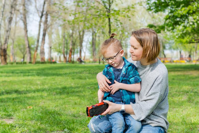 A little boy and his mom play with a toy car in the park in spring. A little boy and his mom play with a toy car in the park on the grass in spring stock photos