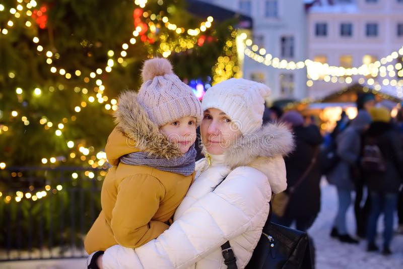 Little boy with his mother or grandmother near giant Christmas fir tree on fair in Tallinn, Estonia royalty free stock images