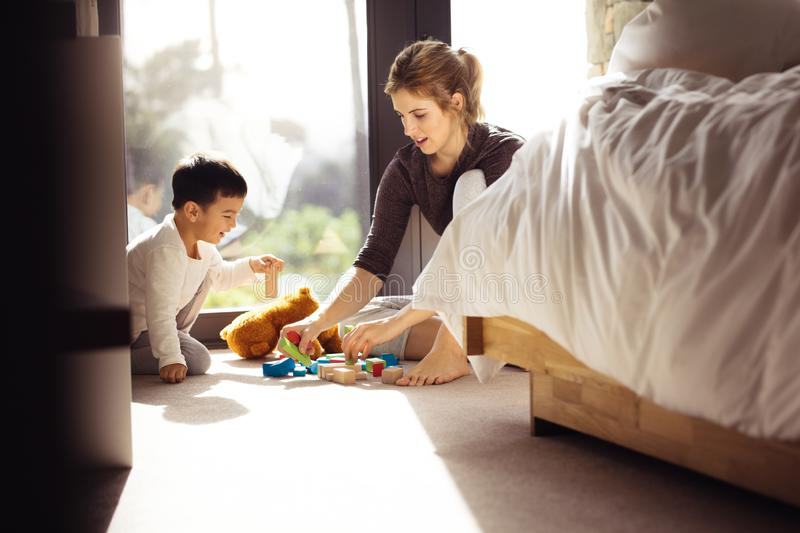 Little boy playing toys with his mother at home royalty free stock photos