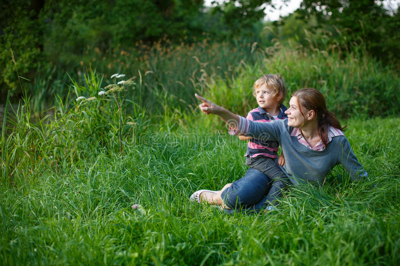 Little boy and his mother sitting on grass in summer forest. Little boy and his mother having fun on grass in summer forest near lake stock image