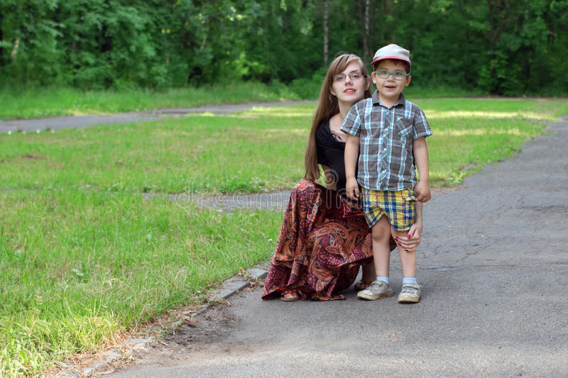 Little boy and his young mother pose in park at sunny d royalty free stock photo