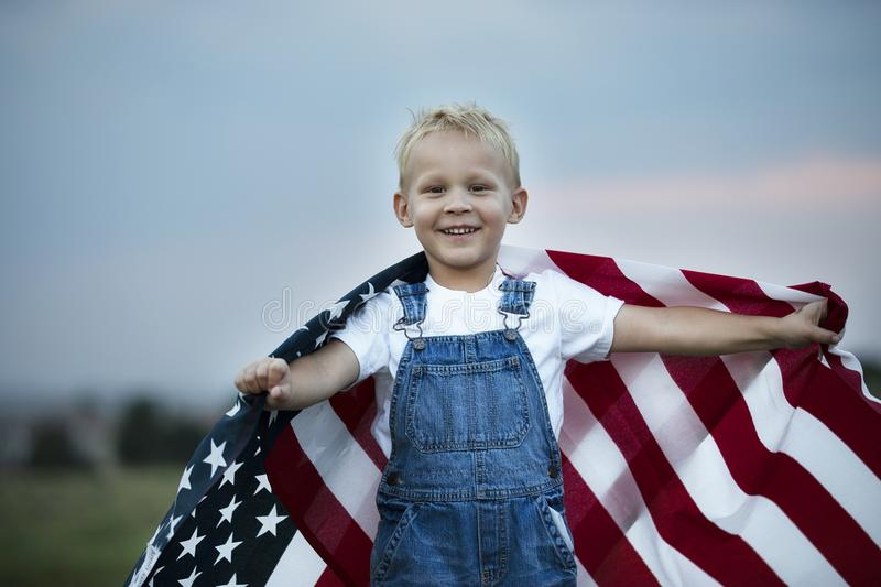 Little boy holding American flag. Little boy is holding American flag. Happy smile face. Patriotic American children. Celebration 4th of July, Independence day stock photo