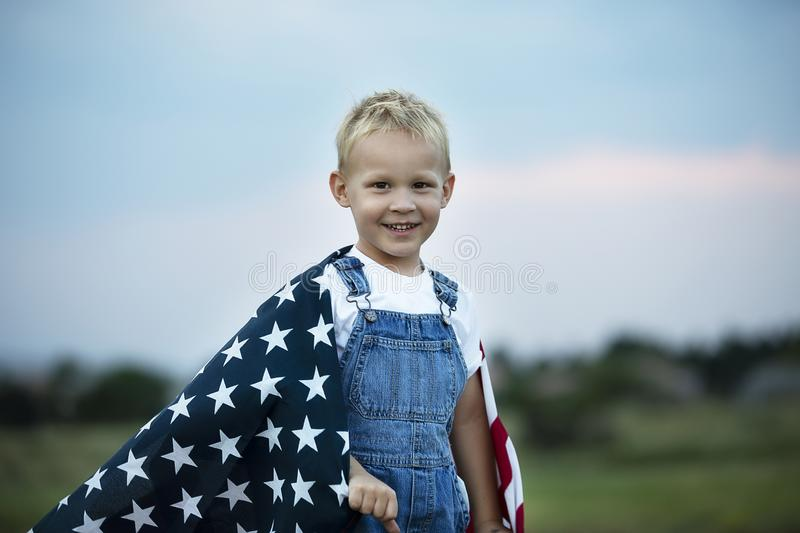 Little boy holding American flag. Little boy is holding American flag. Happy smile face. Patriotic American children. Celebration 4th of July, Independence day stock image