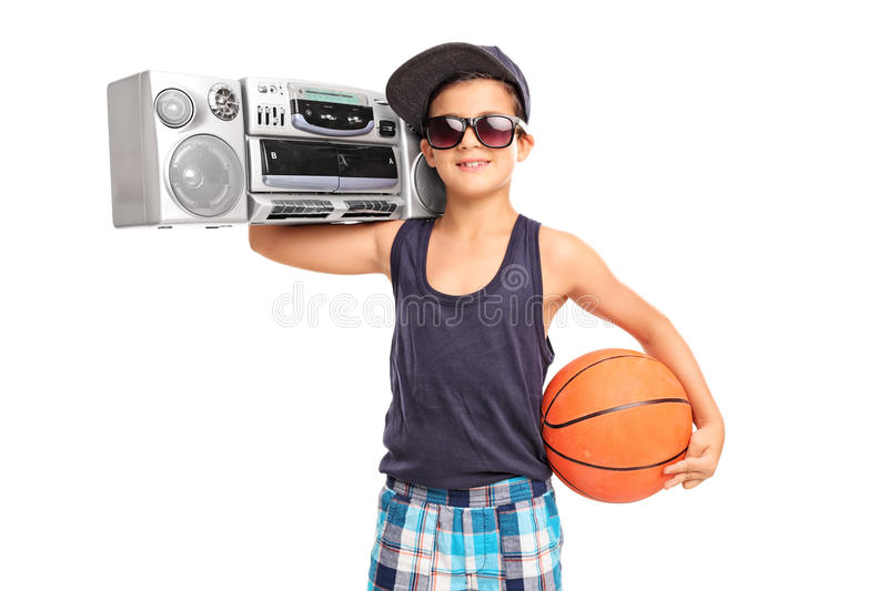 Little boy holding basketball and a ghetto blaster. Studio shot of a little boy holding a basketball and a ghetto blaster isolated on white background stock image