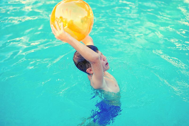 Little boy holding beach ball over head in swimming pool stock photo