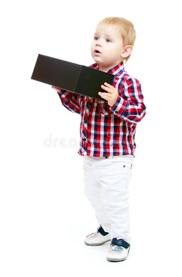 Little boy holding a big black box. Early years learning a happy childhood concept.Isolated on white background royalty free stock photo
