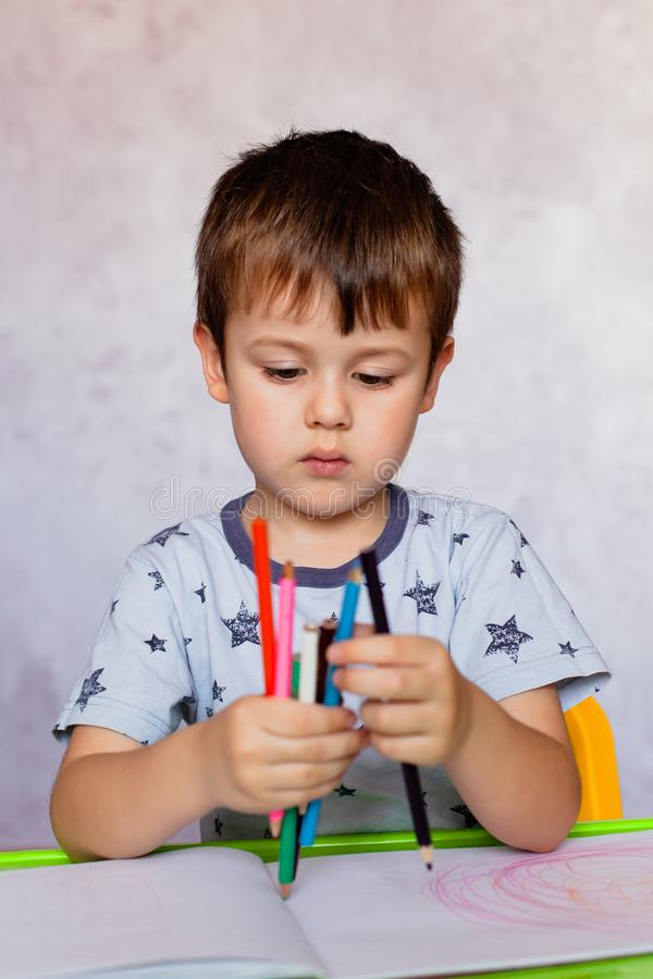 Little boy is holding color pencils. Boy, drawing a picture for fathers day. Small boy draws at the table. Little boy drawing with color pencils. Little boy is stock photo